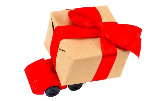 Petite voiture rouge offrant une boîte de cadeaux sur fond blanc.