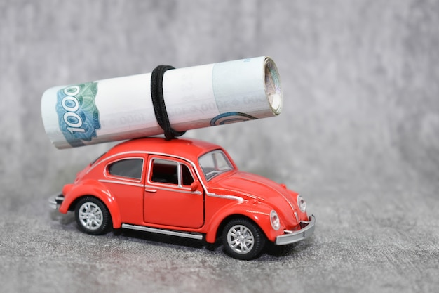 Petite voiture rouge transportant des billets en rouble russe. concept car prêt, assurance, prix de l'essence