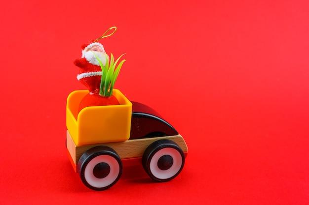 Une petite voiture roule à l'arrière du père noël sur fond rouge du nouvel an.