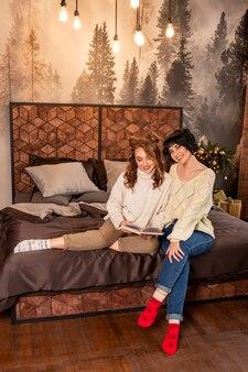 Petites amies assises sur le lit et lisant un livre. ils sourient et célèbrent le nouvel an et noël. filles portant des chandails chauds blancs