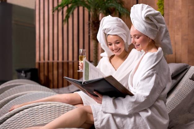 Petites amies dans un salon de spa en serviette et peignoir regardant les prix des procédures buvant du champagne