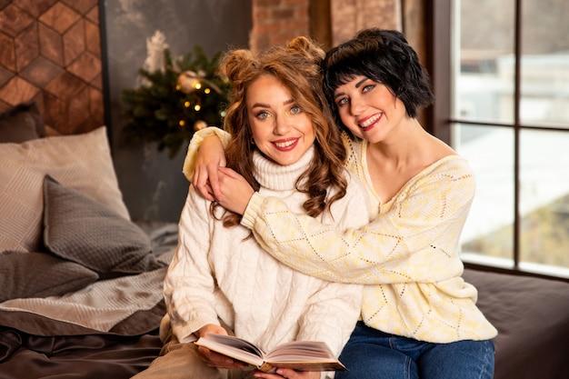 Petites amies étreignant et lisant un livre. ils sourient et célèbrent le nouvel an et noël. filles portant des chandails chauds blancs