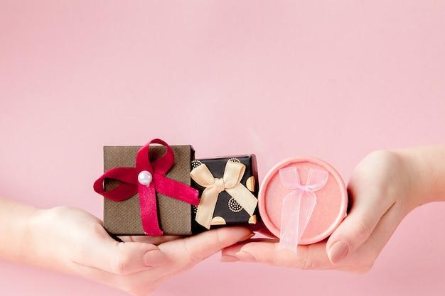 Petites boîtes à cadeaux dans les mains des femmes. concept de fête pour la saint valentin, la fête des mères ou l'anniversaire