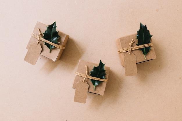 Petites boîtes-cadeaux marron avec des tracts verts