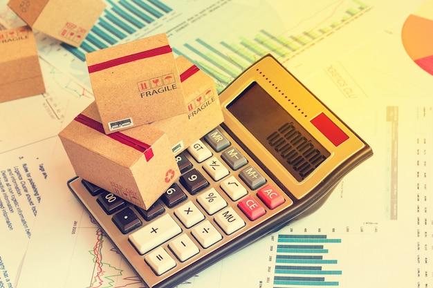 Petites boîtes sur une calculatrice. une idée de marketing les coûts de planification et d'expédition