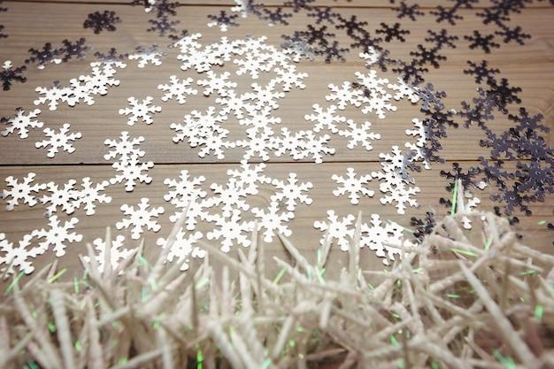Petites bougies et flocon de neige éparpillés sur une table en bois