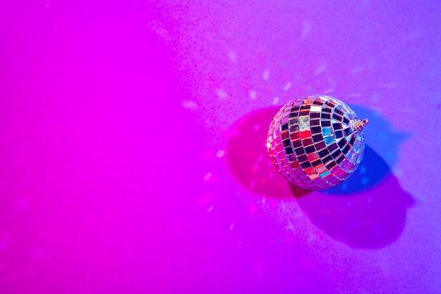 Petites boules disco brillantes étincelantes dans une belle lumière pourpre. concept soirée disco