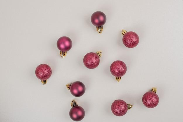 Petites boules de noël rouges sur une surface blanche