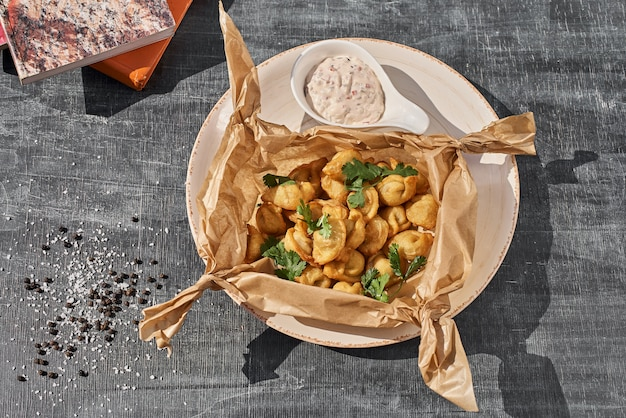 Petites boulettes frites dans une assiette en céramique sur une table