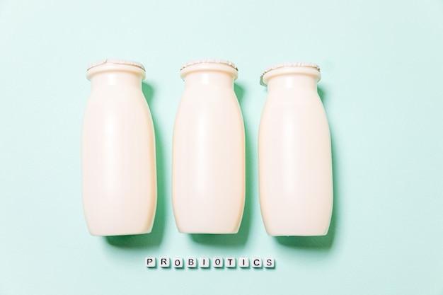 De petites bouteilles de boissons lactées probiotiques et prébiotiques sur fond bleu