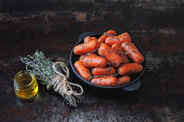 Petites carottes cuites aux herbes dans une poêle en fonte.