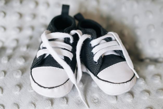 Petites chaussures de bébé. baskets tricotées à la main pour garçon ou fille nouveau-né sur mur gris.