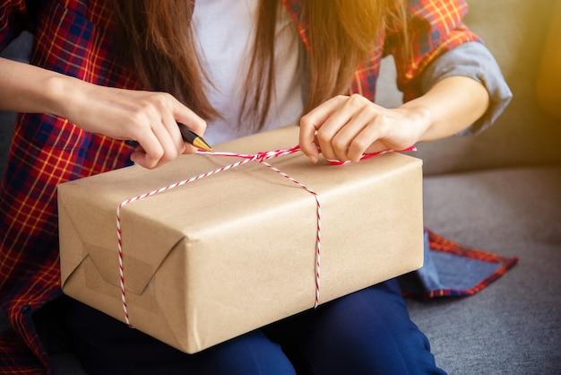 Petites entreprises, vendeur en ligne indépendant, emballant des marchandises dans une boîte pour les livrer au client.