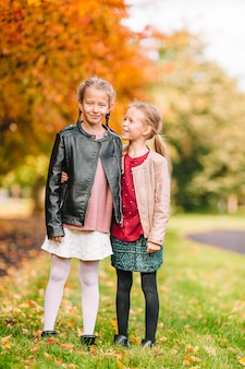 Petites filles adorables au chaud jour d'automne ensoleillé en plein air