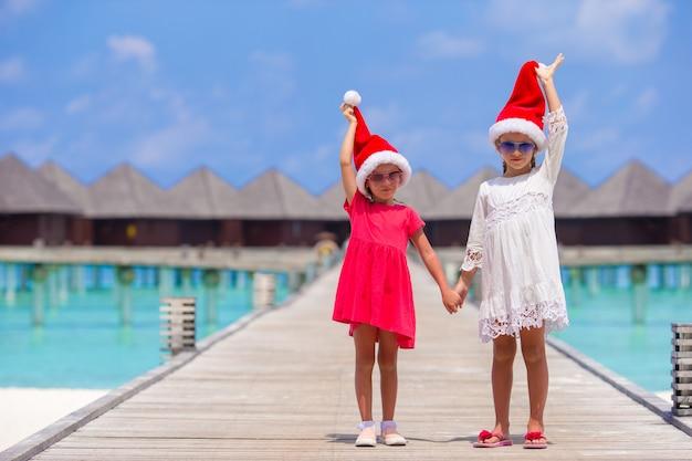 Petites filles adorables chapeaux santa pendant les vacances à la plage à la jetée en bois