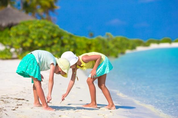 Petites filles adorables, dessin sur la plage blanche