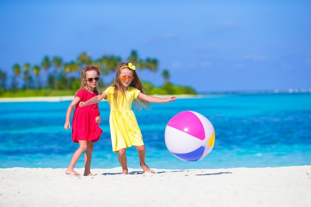 Petites filles adorables jouant sur la plage avec ballon