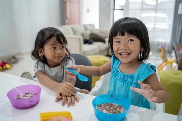 Petites filles asiatiques prenant le petit déjeuner ensemble