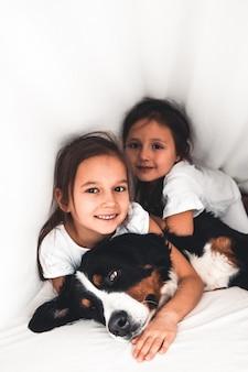 Petites filles au lit avec chien bouvier bernois