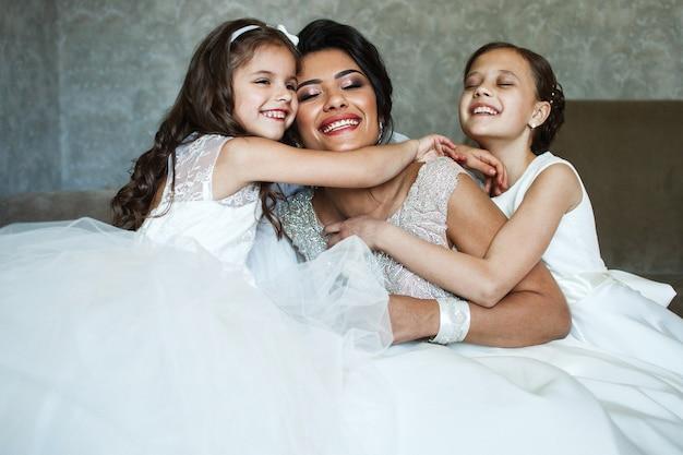 Petites filles câlin mariée tendre debout dans la chambre