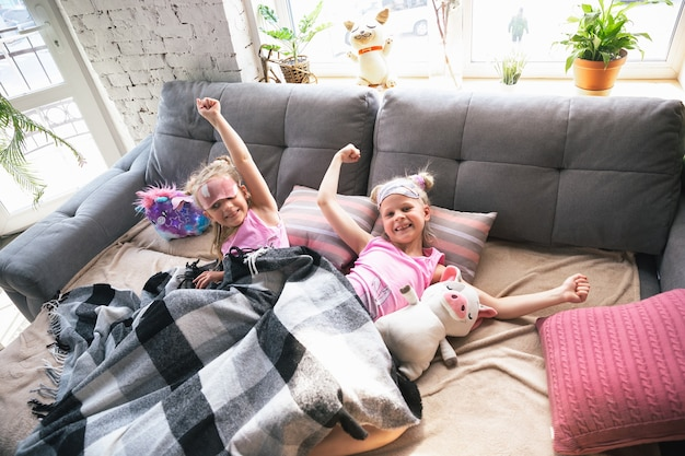 Petites filles calmes jouant dans une chambre en pyjama mignon style maison et confort