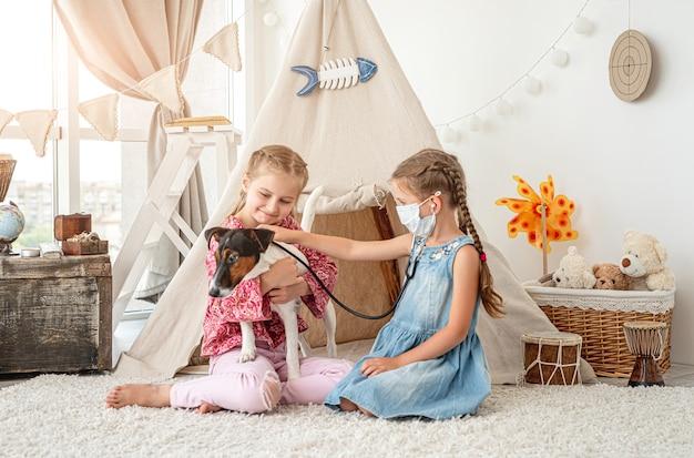 Petites filles avec chien écoute phonendoscope comme médecin assis sur le sol dans la salle de jeux