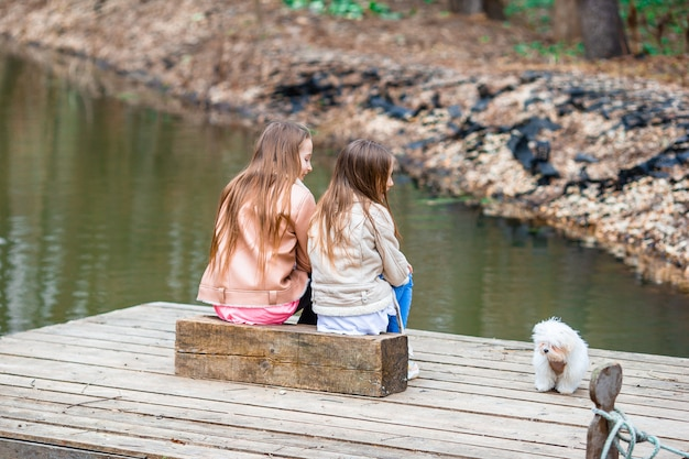 Petites filles avec un chiot blanc. un chiot dans les mains d'une fille