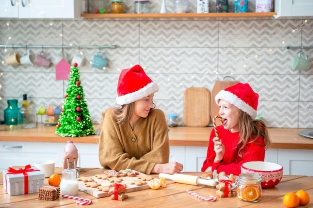 Petites filles la cuisson du pain d'épice de noël. cuisiner et cuisiner avec les enfants pour noël à la maison.