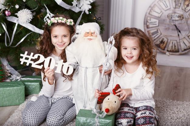 Petites filles dans des vêtements confortables à la maison, assis sur le sol dans de belles décorations de noël.