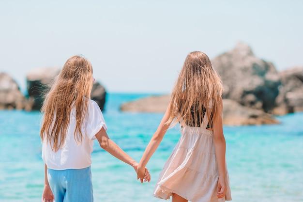 Les petites filles drôles et heureuses s'amusent beaucoup à la plage tropicale en jouant ensemble.