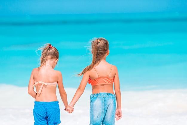 Les petites filles drôles et heureuses s'amusent beaucoup sur la plage tropicale en jouant ensemble.