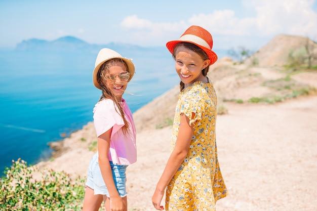Petites filles drôles et heureuses s'amusent beaucoup à la plage tropicale en jouant ensemble