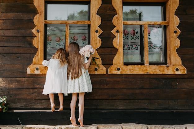 Petites filles espionnage, regardant dans une vieille maison par la fenêtre