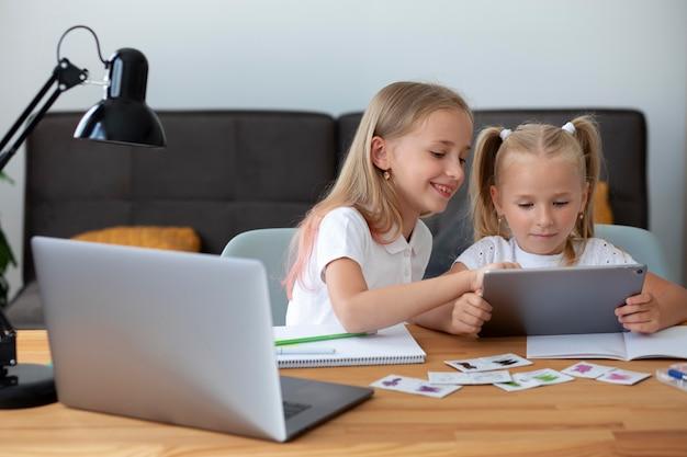 Petites filles faisant l'école en ligne ensemble à la maison