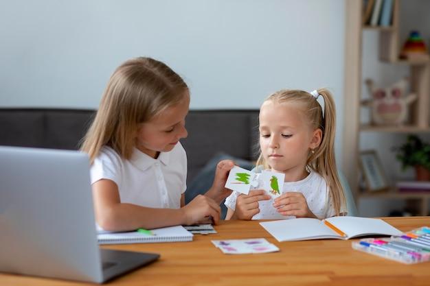Petites filles faisant l'école en ligne ensemble