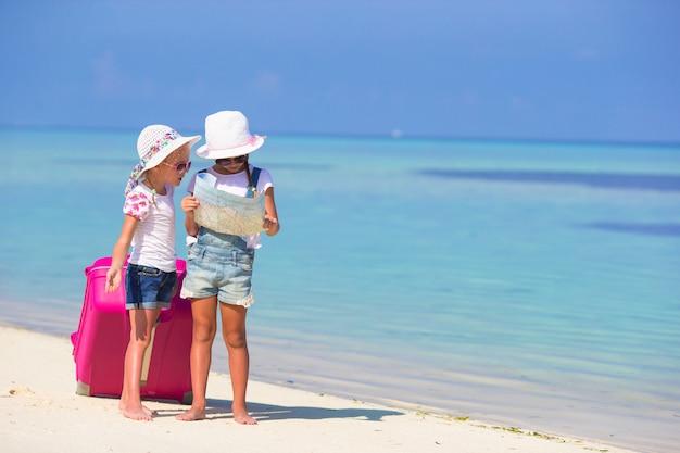 Petites filles avec une grosse valise et une carte sur une plage tropicale
