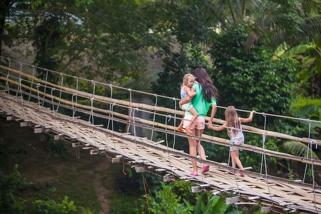 Petites filles et jeune femme marchant sur un pont suspendu sur la rivière loboc, philippines