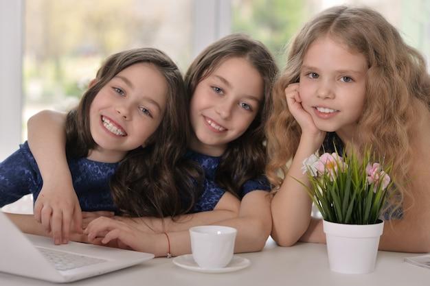 Petites filles jumelles brunes et une petite fille blonde souriante et utilisant un ordinateur portable