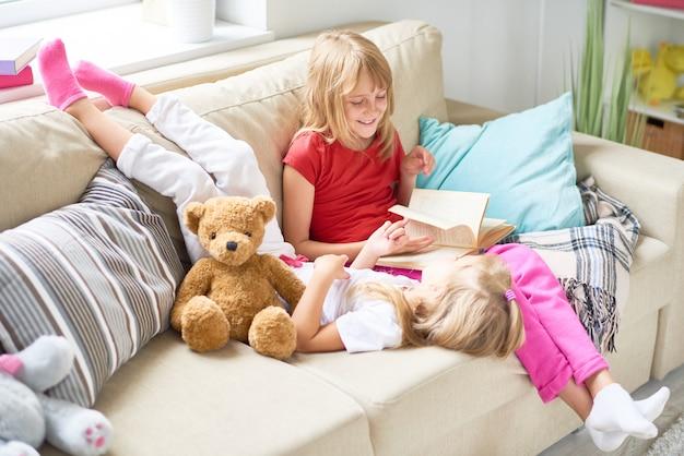 Petites filles lisant des contes de fées à la maison