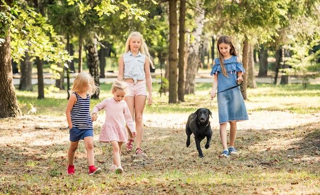 Petites filles marchant avec un chien noir dans un parc