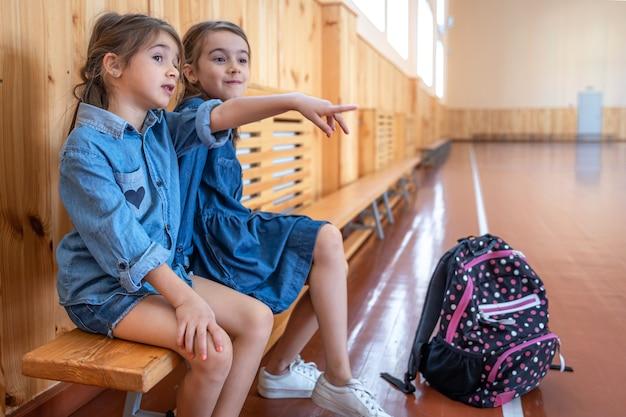 Petites filles mignonnes, écolières du primaire, avec des sacs à dos après l'école dans une salle de gym vide.