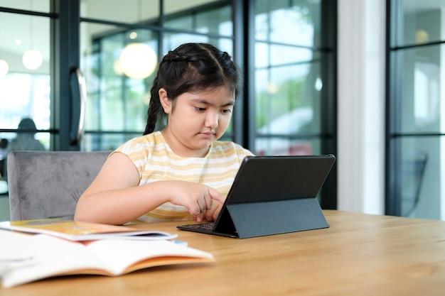Petites filles mignonnes et heureuses utilisant un ordinateur portable, étudiant via un système d'apprentissage en ligne.