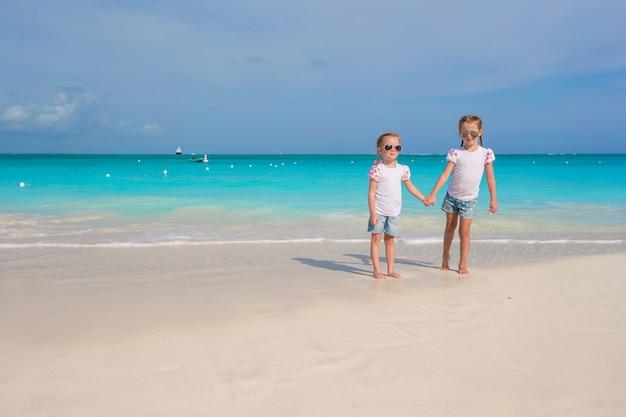Petites filles mignonnes profiter de leurs vacances d'été sur la plage