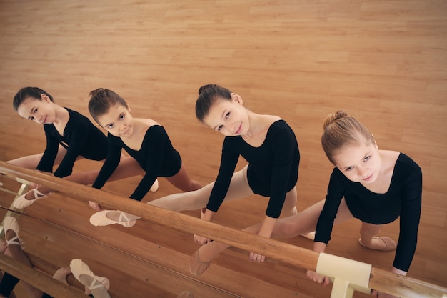 Petites filles mignonnes s'étendant des jambes dans le studio de danse