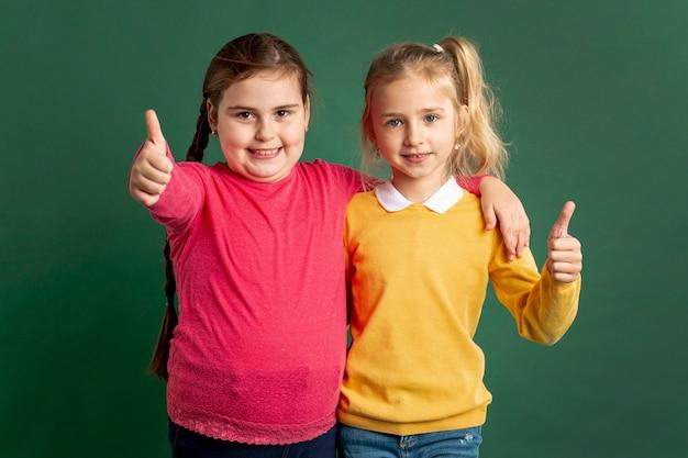 Petites filles montrant signe ok