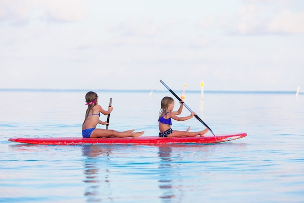 Petites filles nageant sur une planche de surf pendant les vacances d'été