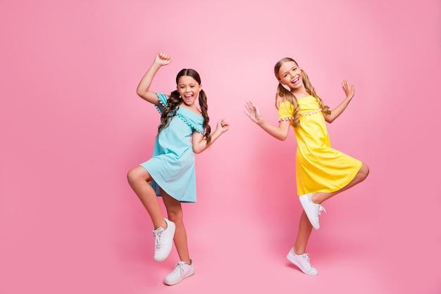 Petites filles avec des nattes posant contre le mur rose