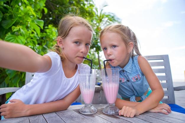 Petites filles prenant selfie et buvant de délicieux cocktails au café en plein air