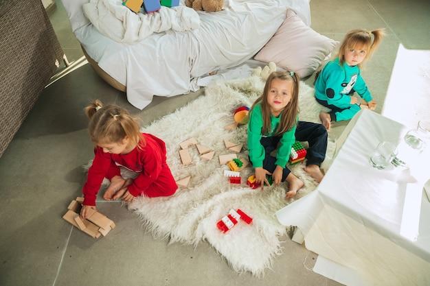 Petites filles en pyjama doux et chaud jouant à la maison