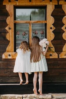 Petites filles à la recherche dans une vieille maison par la fenêtre